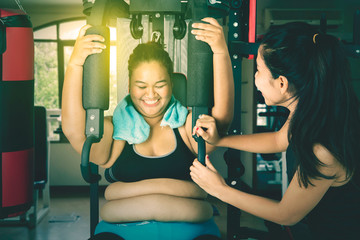 Gym fitness trainer instructing a woman to workout
