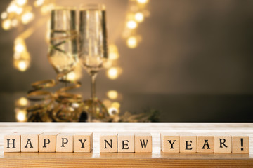 Happy New Year text made out of wooden blocks. Two glasses of champane with festive new year's eve decoration in the background. Copy space in the top right corner.