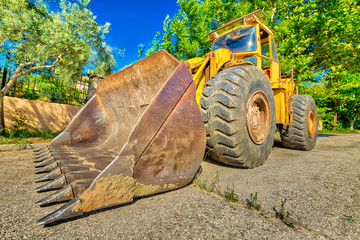 Wide angle and perspective view of heavy and powerful yellow bulldozer excavator on wheels for building work on a road. Work in progress, industrial machine.