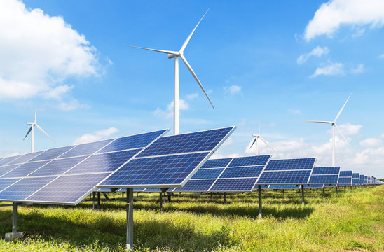 solar cells with wind turbines generating electricity in hybrid power plant systems station on blue sky background alternative renewable energy from nature  Ecology concept.