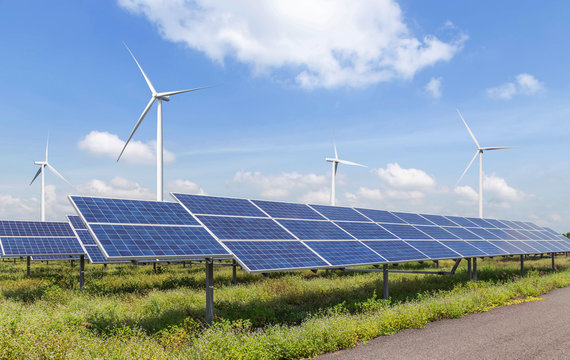 solar cells or solar panels or photovoltaic cells with wind turbines generating electricity alternative renewable wind energy and sunlight energy in hybrid power plant station with blue sky