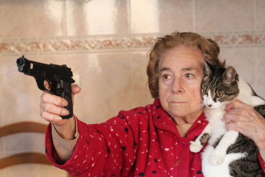 Angry senior woman protecting her cat with a gun