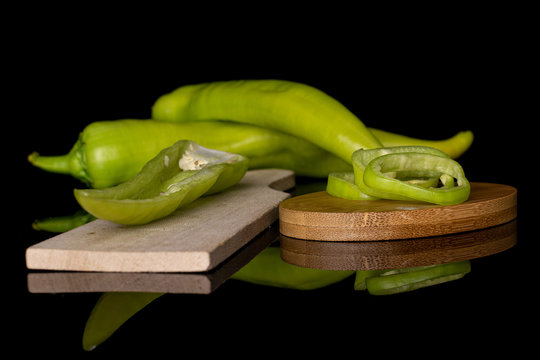 Group of two whole one half three slices of hot green pepper banana on round bamboo coaster on wooden cutting board isolated on black glass
