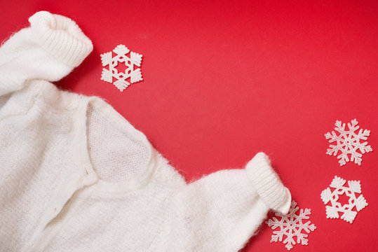 white winter sweater on red background with snowflakes. christmas card with warm clothes
