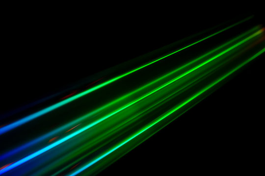 Beams of light refracting and creating a rainbow spectrum of colours against a black background