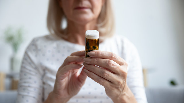 Closeup focus on elderly woman hands holding bottle of pills
