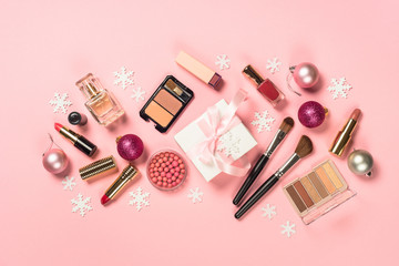 Makeup professional cosmetics with christmas decor on pink.