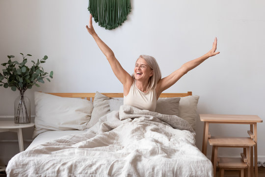 Aged female waking up in morning stretches seated in bed