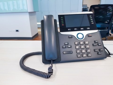 IP phone device on work office table desk background. Communication Technology to connect and call for business use in digital era in corporate company use. Professional device for call, conference.