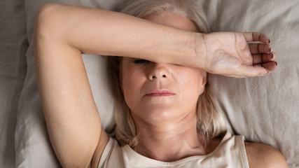 Closeup melancholic woman lying put hand on face feels unwell