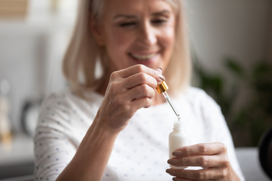 Closeup focus on aged woman hands holding face serum bottle