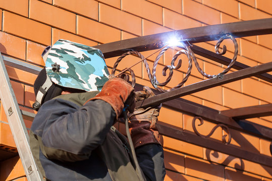 Welder in a protective suit and mask at work