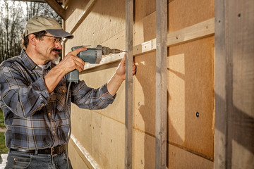 Insulating and Paneling an Outside Wall, Man with Screwdriver