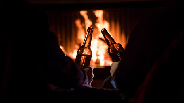 Winter escape - men relax by the fireplace with beer in their hands