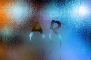 the word ar - augmented reality - written by finger on wet glass with blurred lights in background