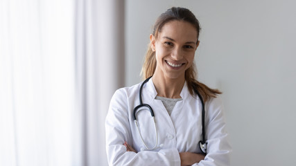 Smiling friendly young female professional confident doctor head shot.