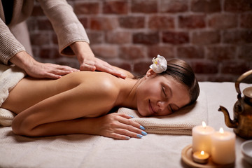 Attractive woman getting spa procedures, back massage by female hands lying on table. Spa,...