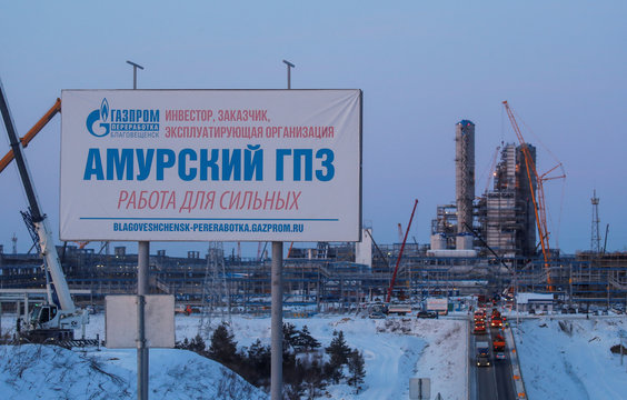 An advertisement billboard is pictured with facilities of Amur gas processing plant under construction in the background, part of Gazprom's Power Of Siberia project outside the far eastern town of Svobodny