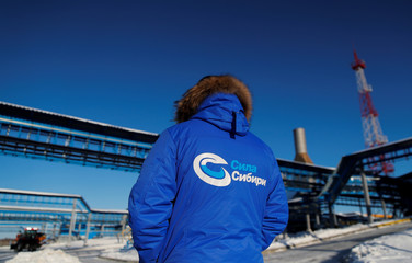 An employee in branded jacket is seen at the Atamanskaya compressor station, facility of Gazprom's Power Of Siberia gas pipeline outside the far eastern town of Svobodny