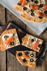 Flat bread with smoked trout, olives and onions