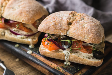 Sandwich with salmon, olives and creamy garlic sauce