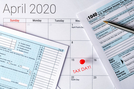 April 2020 calendar with the 15th pinned with tax day text, and 1040 tax forms on the sides.