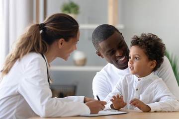 Cheerful young female pediatrician and black father listening to patient.