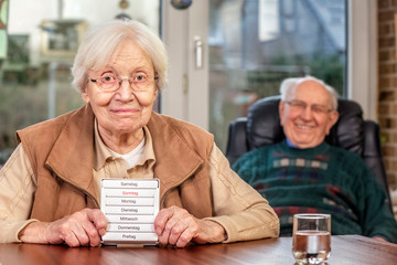 Elderly Woman with Drug Dispenser , Her Husband Sitting in the Background