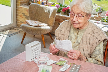 Elderly Woman Reading a Leaflet, Pills on the Table