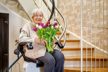 Elderly Woman in the Staircase with Stairlift, Holding a Bouquet of Tulips