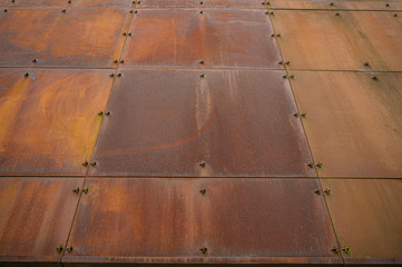 Corner section of a structure made from rusting steel plate.