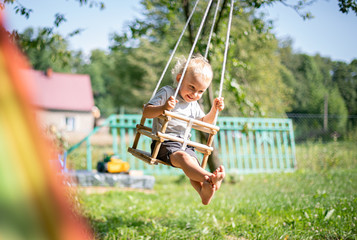 Little boy playing on swing in backyard at coutryside Fotomurales