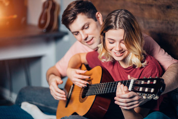 lovely couple, young people playing guitar together at home sitting on bed. caucasian girl and boy wearing casual home clothes