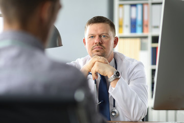 Portrait of concentrated male doctor listening carefully to the patient, propping his head in his hands. Medical treatment and health care concept.