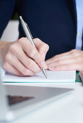 Young businesswoman writing in notepad while sitting at the office. Female hands holding a pen and making notes close up.