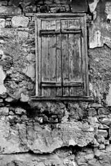 Wall of old house with window closed by shutters