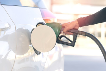 Hand of man and black fuel nozzle filling gas into a white car stopping on a petrol station. (Close-up)