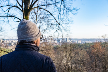 man looking at the city landscape from the forest location