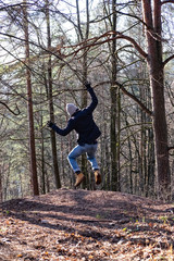 man jumping in the air in the forest