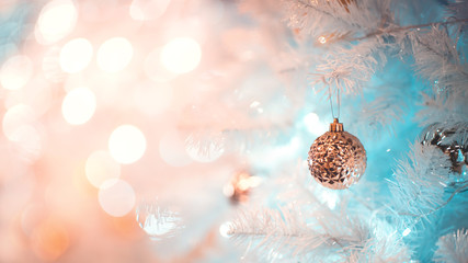 Close up Gold bauble hanging from a decorated Christmas tree with bokeh, copy space. Xmas holiday...