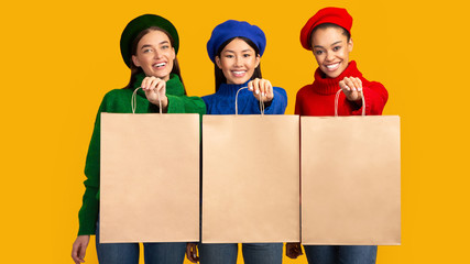 Three Multiethnic Girls Holding Shopper Bags On Yellow Background, Mockup