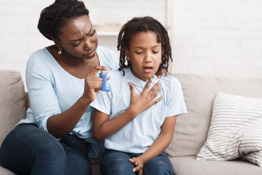 Black mother holding asthma inhaler for daughter