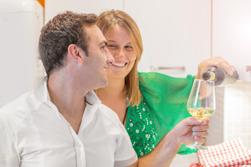 happy couple is drinking a glass of white wine in the kitchen