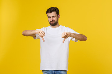 Young handsome man wearing white t-shirt over isolated background Doing thumbs down, disagreement and agreement expression. Crazy conflict.