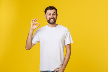 Portrait of a cheerful young man showing okay gesture isolated on yellow background
