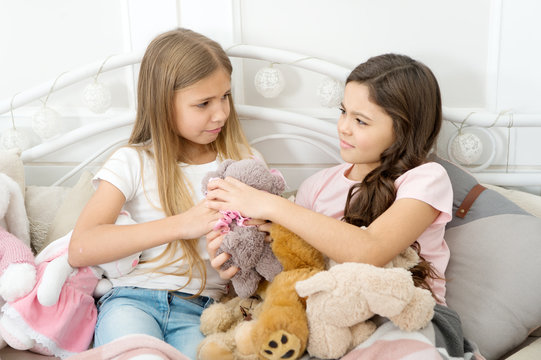 Generosity and greediness. Teach sister sharing toys. Greedy sisters. Kids play toys in bed. Little girls spend time together. Friendship sisterhood personal relations. Toys shop. Cute soft toys