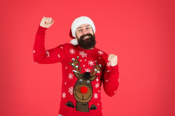 Start this party. Happy new year celebration. Join holiday celebration. Winter party outfit. Sweater with deer. Hipster bearded man wear winter clothes red background. Christmas celebration ideas