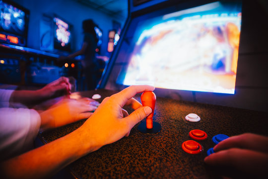 Detail on hands holding joysticks and playing an action game on an old vintage arcade game
