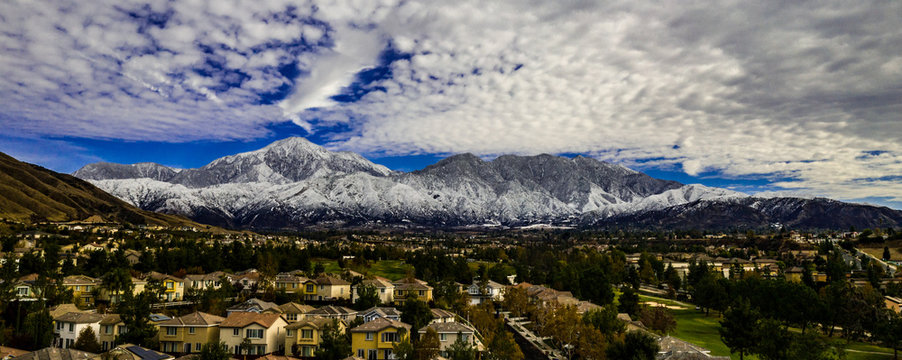 Aerial panorama of snow covered San Gorgonio and Little San Bernardino Mountains on a winter day above Yucaipa Valley with blue sky, white clouds, houses, hills