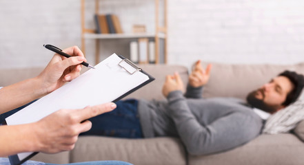 Psychotherapist taking notes, listening to lying on couch patient